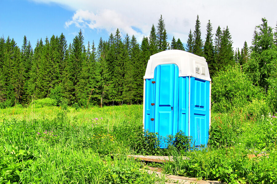 A port-a-potty in a field